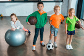 Photo Child lying on fitness ball next to multiethnic children with balls in gym