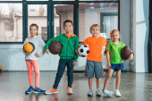 Front view of multiethnic children smiling and holding balls in gym