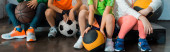 Photo Cropped view of children sitting on step platforms with balls in gym, panoramic shot