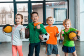 Front view of happy multicultural children holding balls in gym