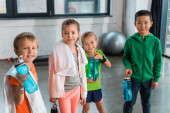 Glückliche multikulturelle Kinder mit Handtüchern, die Sportflaschen in der Turnhalle halten