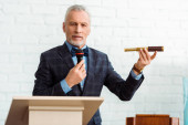 Photo handsome auctioneer in suit talking with microphone and holding spyglass during auction