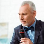 Photo handsome auctioneer in suit talking with microphone during auction