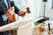 Photo cropped view of auctioneer in suit talking with microphone and holding gavel during auction