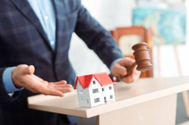cropped view of auctioneer pointing with hand at model of house and holding gavel during auction