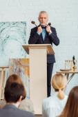 selektiver Fokus des Auktionators mit Hammer und Mikrofon und Blick auf die Käufer während der Auktion