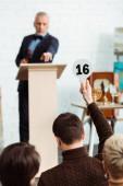 zpětný pohled kupujícího předvádějícího aukční pádlo s číslem 16 dražiteli během aukce