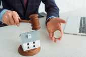 Photo cropped view of auctioneer hitting model of house with gavel and holding coins