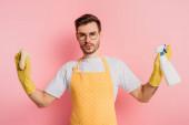 ernster junger Mann in Schürze und Gummihandschuhen mit Sprühflasche und Lappen auf rosa Hintergrund