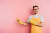 glücklicher junger Mann in Schürze und Gummihandschuhen zeigt mit Fingern auf rosa Hintergrund