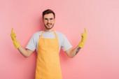 fröhlicher junger Mann in Schürze und Gummihandschuhen zeigt mit Fingern auf rosa Hintergrund