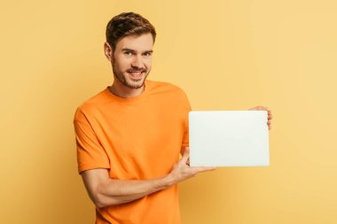 Smiling young man showing closed laptop and looking at camera on yellow background stock vector