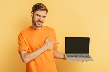 cheerful young man pointing with finger at laptop with blank screen on yellow background