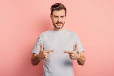 smiling handsome man showing gun gestures while looking at camera on pink background