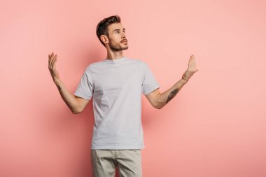 dreamy young man looking up while standing with open arms on pink background
