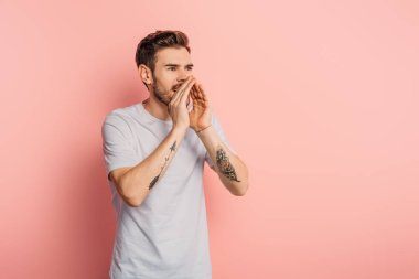 excited young man screaming while holding hand near mouth on pink background