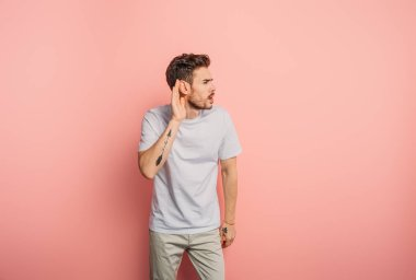 Confused young man showing cant hear gesture by holding hand near ear on pink background stock vector