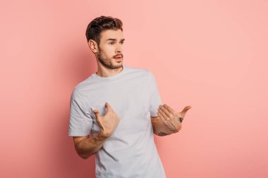 shocked young man looking away and pointing with hands at himself on pink background