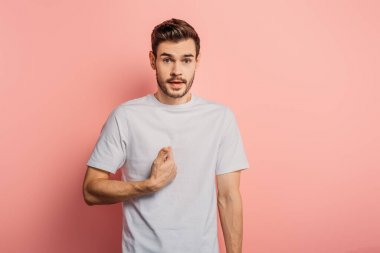 surprised young man pointing with hand at himself while looking at camera on pink background