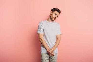 offended young man looking at camera while standing on pink background