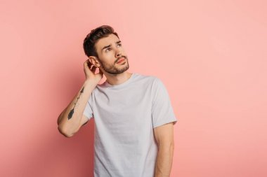 dreamy young man touching head and looking up on pink background