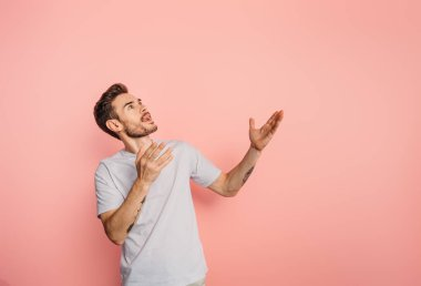 amazed young man looking up while standing with open arms on pink background