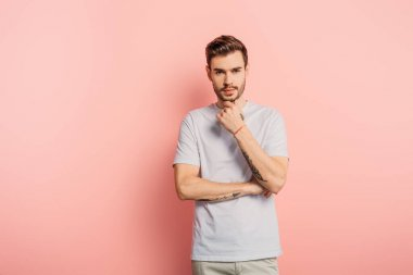 thoughtful young man touching chin while looking at camera on pink background