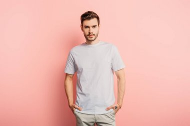 handsome, confident young man with hands in pockets looking at camera on pink background