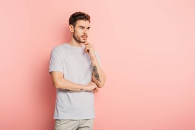 handsome pensive man looking away and touching chin on pink background