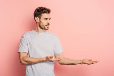 handsome confident man looking away and pointing with hands on pink background