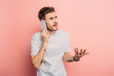 shocked young man standing with open arm while talking on smartphone on pink background