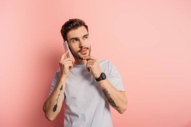 Pensive young man touching chin while talking on smartphone on pink background stock vector