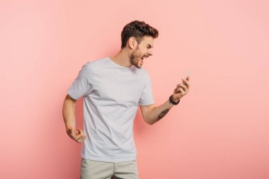 irritated young man screaming while having video call on smartphone on pink background
