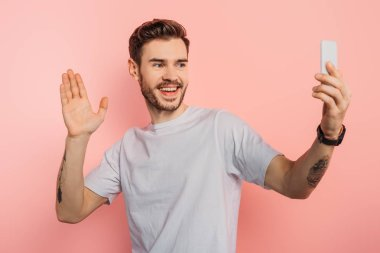 excited young man waving hand while having video chat on smartphone on pink background