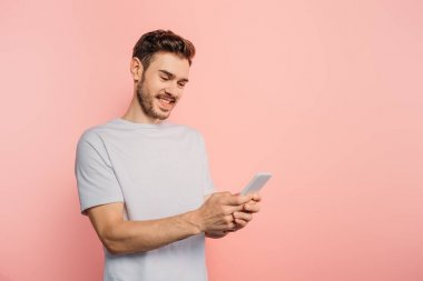 happy young man chatting on smartphone on pink background