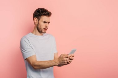 shocked young man chatting on smartphone on pink background