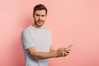shocked young man looking at camera while chatting on smartphone on pink background
