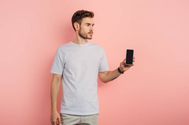 confident young man showing smartphone with blank screen and looking away on pink background