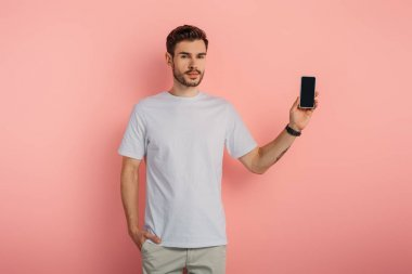 handsome confident man with hand in pocket showing smartphone with blank screen on pink background