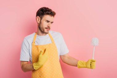 confused young man in apron and rubber gloves pointing with hand at himself while looking at toilet brush on pink background