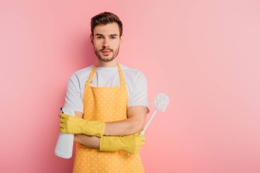 serious young man in apron and rubber gloves holding spray bottle and toilet brush on pink background