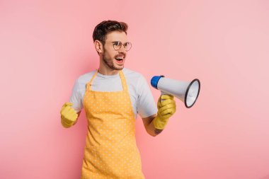 irritated young man in apron and rubber gloves screaming in megaphone on pink background