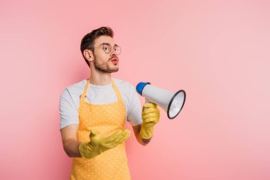 displeased young man in apron and rubber gloves holding megaphone while standing with open arm on pink background