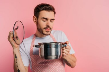 Pleased young man in apron enjoying flavor with closed eyes while opening saucepan on pink background stock vector