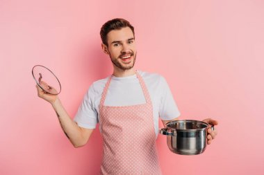 Cheerful young man in apron opening saucepan on pink background stock vector