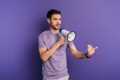 Fotografie seriózní mladý muž ukazuje přijít sem gesto, zatímco drží megafon na fialovém pozadí