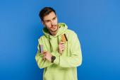 zamyšlený mladý muž dívá pryč, zatímco drží kreditní karty na modrém pozadí