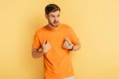dühös fiatalember mutat magát az ujjaival, miközben félrenéz sárga háttér
