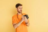 pohledný pozorný fotograf při pohledu na digitální fotoaparát na žlutém pozadí