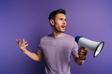 Shocked young man holding megaphone and looking away on purple background stock vector